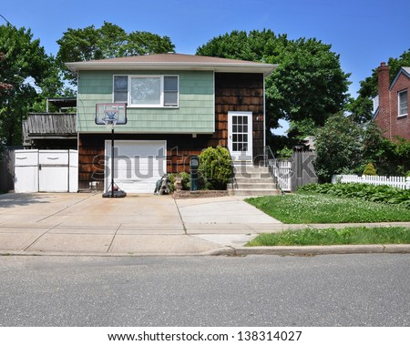 Suburban Middle Class Home in Residential Neighborhood Basketball Hoop in Driveway - stock photo