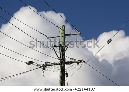 Suburban power lines and pole with fluffy  white cumulus  cloud formations   with some cumulonimbus on  a sunny afternoon  in late autumn   are contrasted against the blue Australian sky. - stock photo