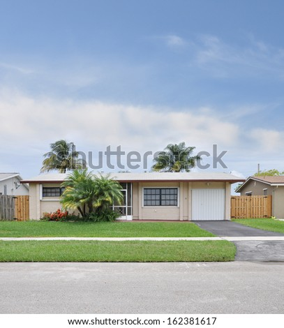 Suburban Ranch Style Home Tropical Climate Residential Neighborhood Blue Sky Clouds Palm Trees Daytime USA - stock photo
