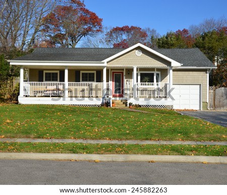 Suburban Ranch style home with porch sunny autumn day residential neighborhood clear blue sky USA - stock photo