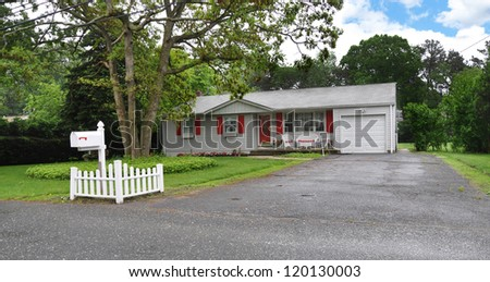 Suburban Ranch Style Home with Red Shutters wet blacktop driveway - stock photo