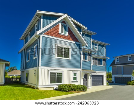Suburban residential house with garage on a street. Facade of family house with green lawn in front and blue sky background - stock photo