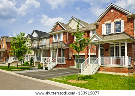 Suburban residential street with row of red brick houses - stock photo