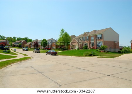 Suburban street and homes in the summertime. - stock photo