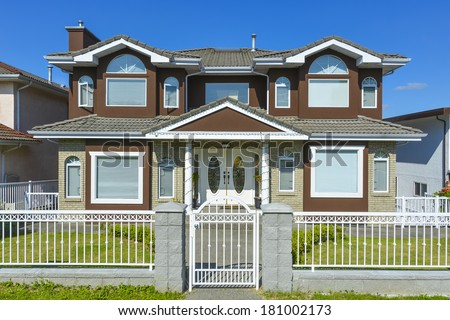 Suburban Vancouver house with metal fence and gate in front and blue sky background. - stock photo