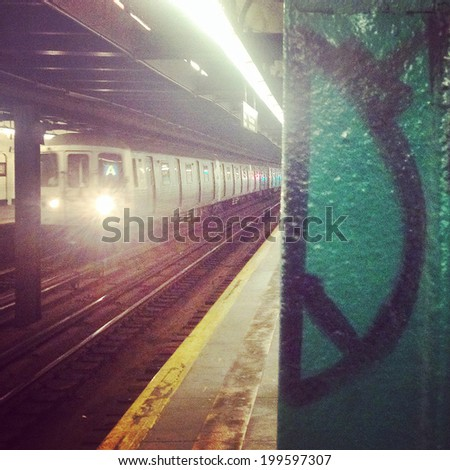 "Subway car traveling in motion underground with visible ""peace sign"" graffiti on pole in New York City with Instagram effect filter. - stock photo"