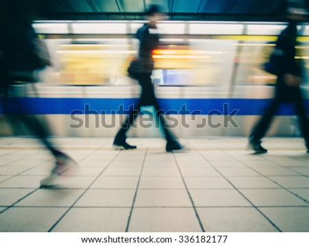 Subway train leaving station. People coming to or leaving the platform. Motion blur. City life. Slightly blue-toned. - stock photo