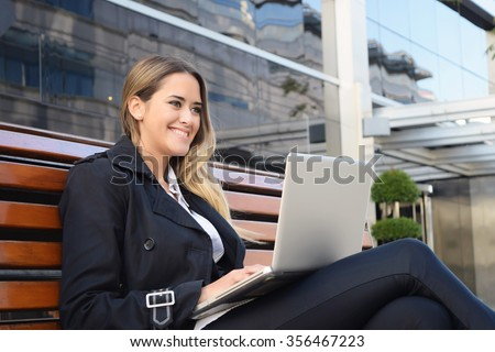 Succesful business woman working on a laptop outside her office. - stock photo