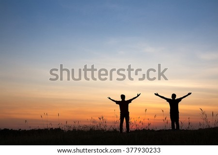 Success, achievement and accomplishment concept with hiking people cheering and celebrating of joy with arms raised outstretched up in the sky on trekking hike outside. Hikers having fun at sunset. - stock photo