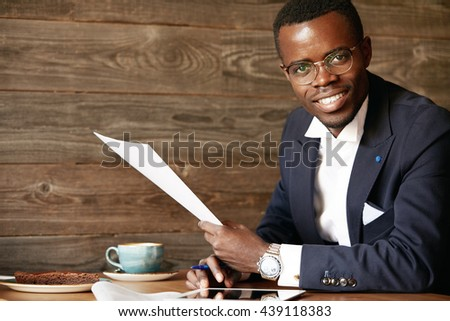Success and achievement. Happy African businessman in glasses looking the camera with cheerful ultra-white smile, signing a profitable contract, achieving business goals while sitting at a cafe - stock photo