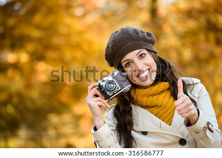 Success and happiness in autumn. Woman holding camera and doing thumbs up success gesture against fall season colors foliage background. Fashionable girl wearing scarf, raincoat and cap. - stock photo