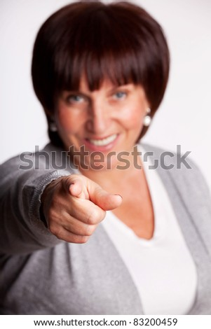 Success and happy mid adult woman. Focus on the forefinger - stock photo