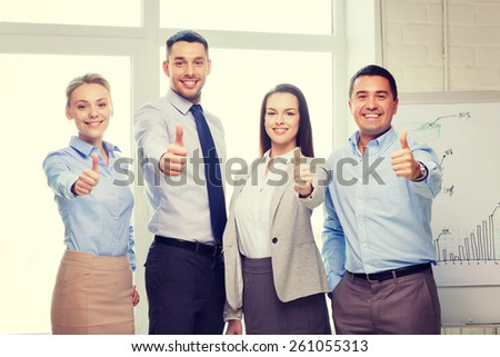 success, business, office and winning concept - happy business team showing thumbs up in office - stock photo