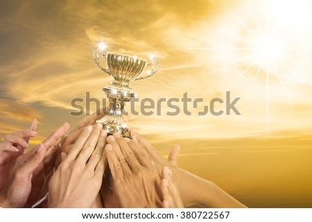 Success business with their winner trophy holding by hands.  - stock photo