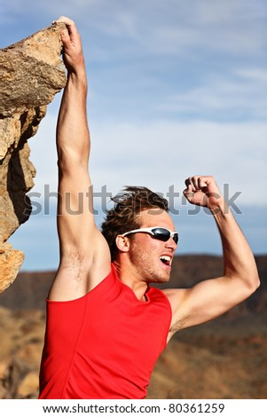 Success concept - man climbing, hanging on edge showing strength and muscles. Strong successful male climber. - stock photo