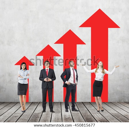 Success concept with young businesspeople and red arrow chart in room with wooden floor and concrete wall - stock photo