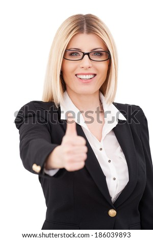 Success. Confident mature businesswoman showing her thumb up and smiling while standing isolated on white - stock photo
