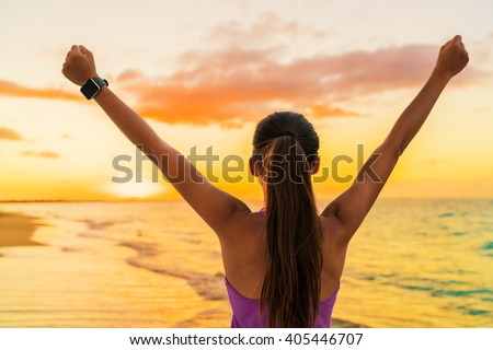 Success freedom smartwatch woman from behind at sunset. Winning goal achievement fitness athlete girl cheering on tropical summer beach wearing wearable tech smart watch activity bracelet. - stock photo