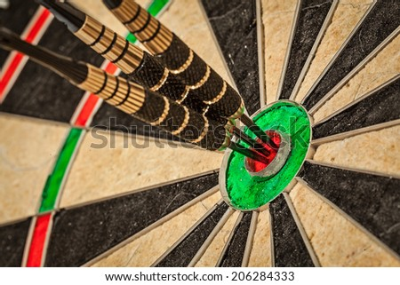 Success hitting target aim goal achievement concept background - three darts in bull's eye close up - stock photo