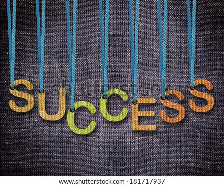 Success Letters hanging strings with blue sackcloth background. - stock photo
