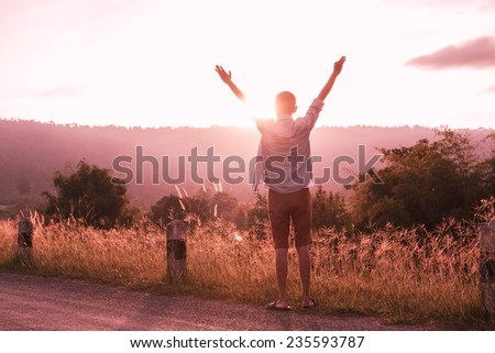 success man hold up hands to sun light,color process - stock photo