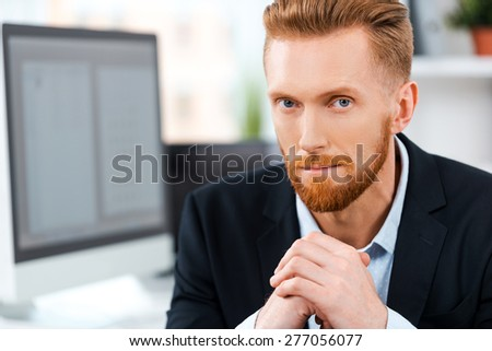 Success starts with your attitude. Serious young bearded businessman keeping hands clasped and looking at camera while sitting at his working place - stock photo