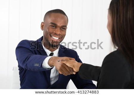 Successful African American Businessman Handshaking With Client In Office - stock photo