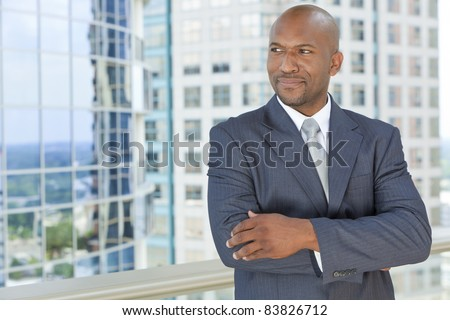 Successful African American businessman or man arms folded in a suit in a modern city - stock photo