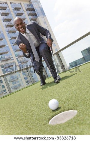 Successful African American businessman or man in a suit playing golf on a corporate putting green on roof of a skyscraper office building - stock photo