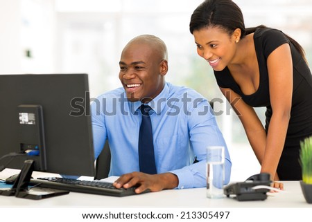 successful african secretary with her boss working on computer - stock photo
