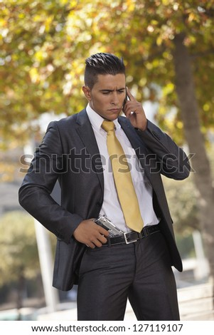 Successful and handsome businessman talking at his cellphone - stock photo