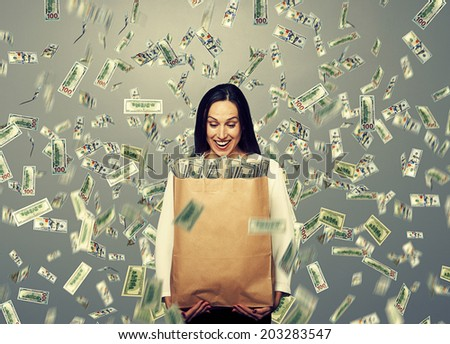 successful and smiley businesswoman holding paper bag with money under dollar's rain - stock photo