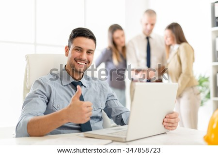 Successful arabian businessman showing thumbs up in the office and looking at camera. His colleagues, in the background, consider the project. Looking at camera. - stock photo