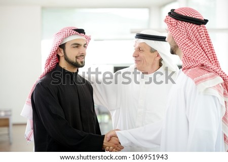 Successful Arabic business people shaking hands over a deal - stock photo