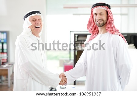 Successful Arabic business people shaking hands over a deal in office - stock photo