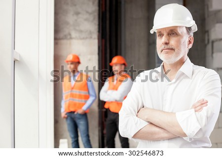 Successful architect is standing and relaxing. He is closing his hands and looking through the window dreamingly. The builders are standing behind him. Copy space in left side - stock photo