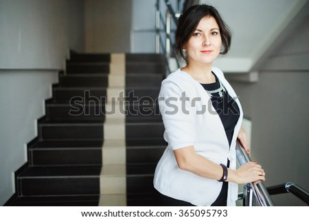 Successful attractive brunette with kind eyes standing on the stairs of office building, during a break at work. Wearing a white jacket and a strict black dress with jewelry. Cute young woman posing. - stock photo