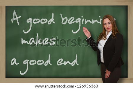 Successful, beautiful and confident woman showing A good beginning makes a good end on blackboard - stock photo