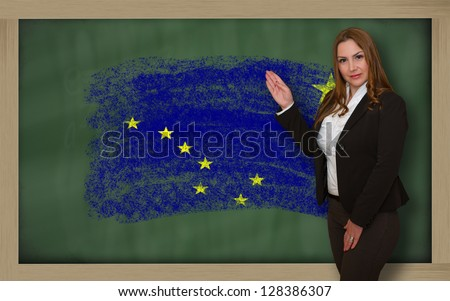 Successful, beautiful and confident woman showing flag of alaska on blackboard for marketing research, presentation and tourist advertising - stock photo