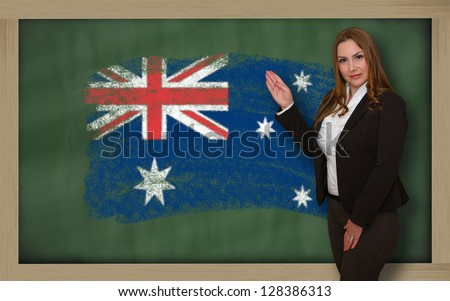 Successful, beautiful and confident woman showing flag of australia on blackboard for marketing research, presentation and tourist advertising - stock photo