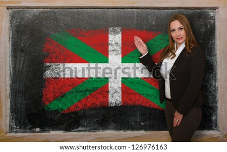 Successful, beautiful and confident woman showing flag of basque on blackboard for marketing research, presentation and tourist advertising - stock photo