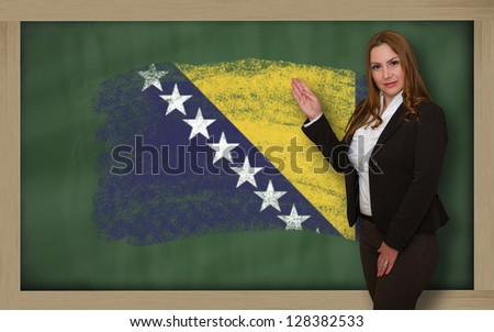 Successful, beautiful and confident woman showing flag of bosnia herzegovina on blackboard for marketing research, presentation and tourist advertising - stock photo