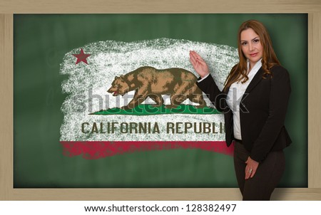 Successful, beautiful and confident woman showing flag of california on blackboard for marketing research, presentation and tourist advertising - stock photo