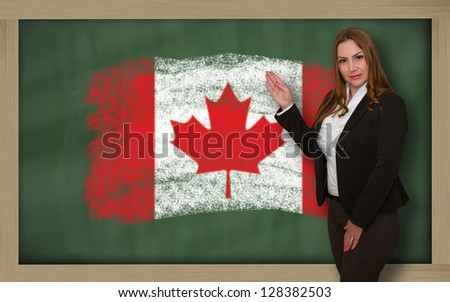 Successful, beautiful and confident woman showing flag of canada on blackboard for marketing research, presentation and tourist advertising - stock photo