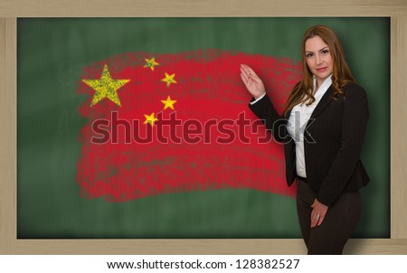 Successful, beautiful and confident woman showing flag of china on blackboard for marketing research, presentation and tourist advertising - stock photo