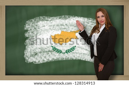 Successful, beautiful and confident woman showing flag of cyprus on blackboard for marketing research, presentation and tourist advertising - stock photo