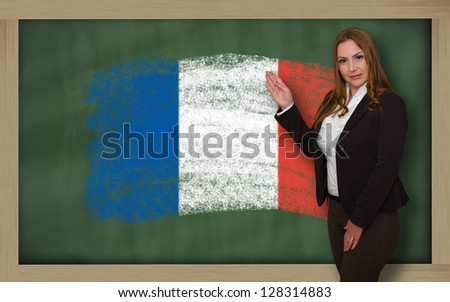Successful, beautiful and confident woman showing flag of france on blackboard for marketing research, presentation and tourist advertising - stock photo