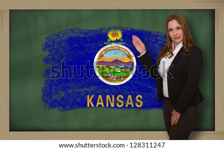 Successful, beautiful and confident woman showing flag of kansas on blackboard for marketing research, presentation and tourist advertising - stock photo