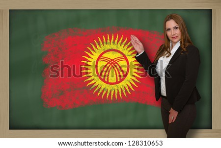 Successful, beautiful and confident woman showing flag of kirghizstan on blackboard for marketing research, presentation and tourist advertising - stock photo