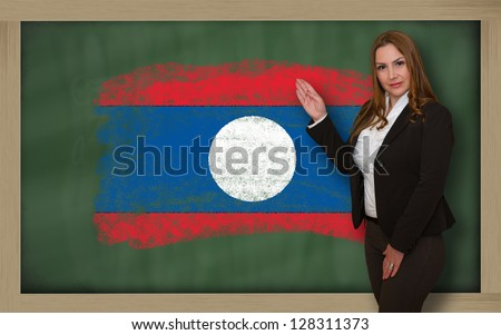 Successful, beautiful and confident woman showing flag of laos on blackboard for marketing research, presentation and tourist advertising - stock photo
